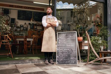 카페의 문에 서있는 젊은 웨이터의 전체 길이 촬영. 그녀의 팔을 서 앞치마를 입고 수염을 가진 젊은 남자가 건너와 멀리보고.