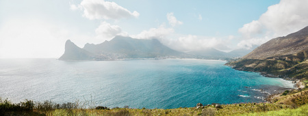 cloudscapes: Panoramic shot of beautiful Hout Bay from Chapmans peak Drive on atlantic coast of South Africa. Bay of water, mountain range and cloudscapes.