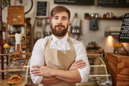 젊은 남자가 그의 팔을 서 앞치마를 입고의 초상화 커피 숍에서 교차. 수염 카메라를 찾고 카페에 서있는 백인 남자.