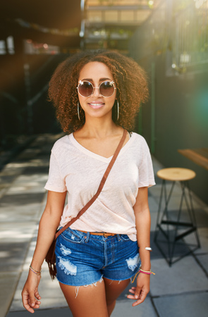 casuals: Stylish african woman wearing sunglasses posing outdoors. Beautiful young girl with curly hair in casuals walking on sidewalk.