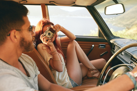 Caucasian couple going on a road trip. Woman taking pictures with camera and man driving car.