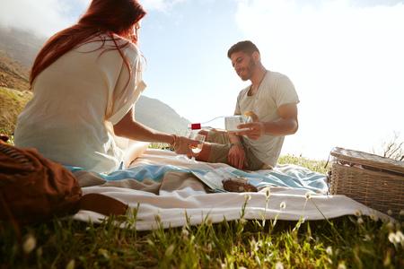 tomando vino: Hombre joven verter el vino en copas mientras estaba sentado con su novia. Joven pareja de beber vino y disfrutar de un picnic al aire libre. Foto de archivo