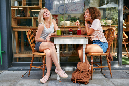 Two young friends sitting at outdoor cafe and smiling. Multiracial women hanging out at sidewalk restaurant.