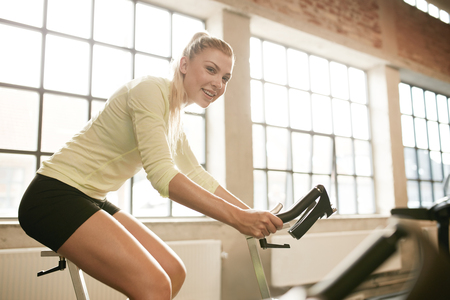 one woman: Indoor shot of a sportive woman on bicycle in gym. Young female athlete working out on spinning bike at health club. Stock Photo