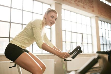 mujer deportista: Tiro de interior de una mujer deportiva en la bicicleta en el gimnasio. Mujer atleta joven que se resuelve en bicicleta de spinning en el gimnasio.