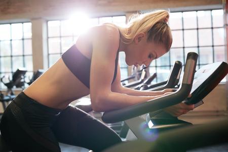 motion: Kvinnan tar paus under cykling träningspass i gymmet. Kvinna på gym cykel gör konditionsträning. Stockfoto
