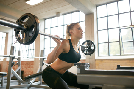 Female exercising in gym doing squats with extra weight on her shoulders. Young woman working out with heavy weights in a fitness club.
