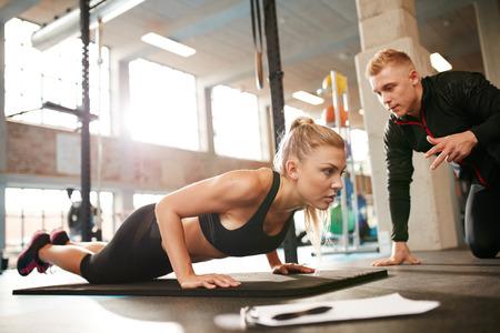 フィットネス: ジムで個人トレーナーと若い女性運動の屋内撮影。プッシュを行うフィットネス女性健康クラブで彼女のパーソナル トレーナーとの連携。