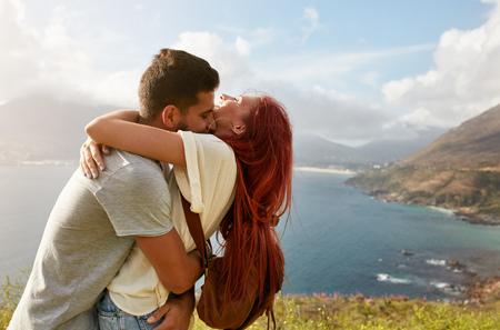 Liefdevolle jonge paar omhelzen en kussen op een zomerse dag in de buitenlucht. Man knuffelen zijn vriendin. Genieten van hun zomervakantie.