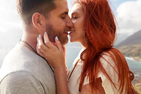 novios besandose: Cierre de tiro de joven pareja cari�osa abrazando y besando al aire libre.