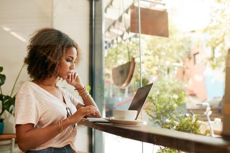 노트북을 사용하는 카페에서 젊은 흑인 여성. 그녀의 노트북에있는 식당 바쁜 작업에 앉아 아프리카 젊은 여자. 스톡 콘텐츠