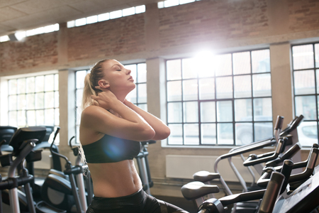 self conscious: Young woman tired after intense workout on gym bike. Relaxing her neck muscles after workout in fitness club.