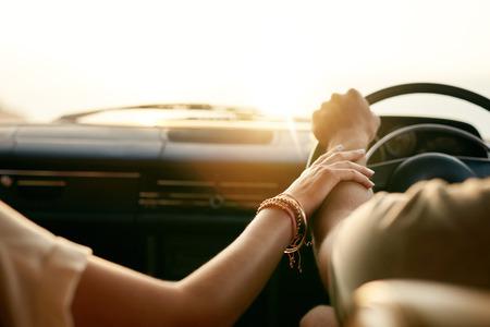 personas unidas: Vista trasera de una joven pareja cogidos de la mano mientras est� sentado en su coche juntos. Hombre y mujer en un viaje por carretera.