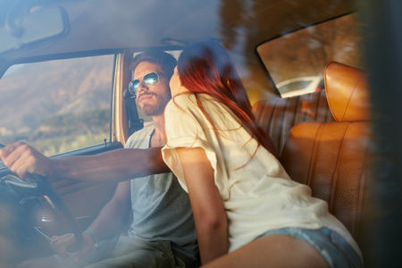 romantic man: Woman kissing man driving car. Couple on road trip. Romantic caucasian couple on holiday having fun in car.