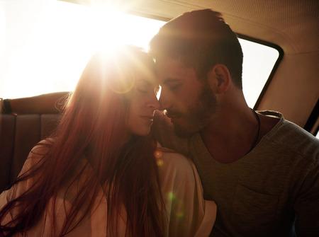 femme romantique: Romantique jeune couple assis dans le si�ge arri�re d'une voiture. Jeune couple sentiment romantique dans le si�ge arri�re d'un v�hicule avec le soleil pouss�e par derri�re.