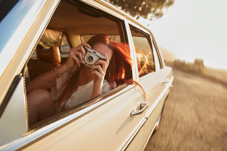 day trip: Shot of  young woman taking photos while sitting in a car. Female capturing a perfect road trip moment.