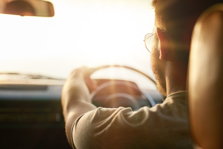 young man smiling: Close up shot of young man driving car. Rear view of man on road trip on a summer day, with sun flare. Stock Photo