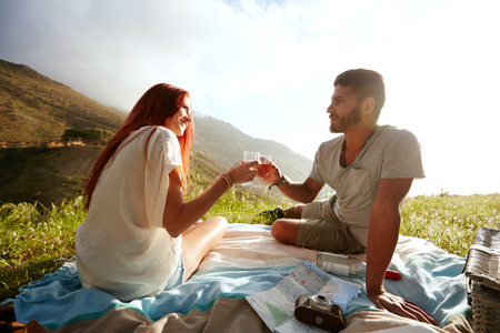 vacation summer: Love couple sitting on the grass and drinking wine during a picnic. Caucasian man and woman on summer holiday. Couple having a romantic day outdoors