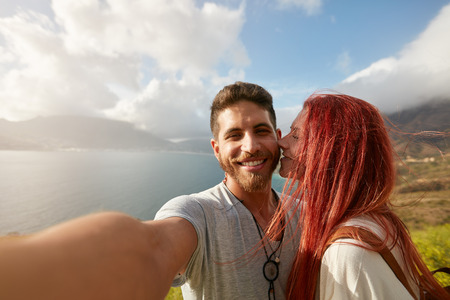 couple nature: Young couple taking a selfie outdoors. POV shot man holding a camera and taking a self portrait with woman kissing him. Stock Photo