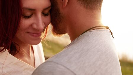 close up eyes: Close up shot of affectionate young woman embracing her boyfriend with her eyes closed. Romantic young couple together outdoors on a summer day.