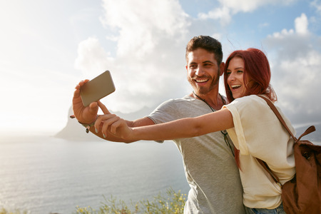 people  camera: Laughing young couple on holidays making selfie with mobile phone. Young couple by the bay taking a selfie portrait with smart phone. Stock Photo