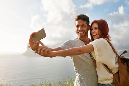 parejas felices: Riendo joven pareja en las vacaciones haciendo selfie con el tel�fono m�vil. Pareja joven por la bah�a de tomar un retrato selfie con el tel�fono inteligente.