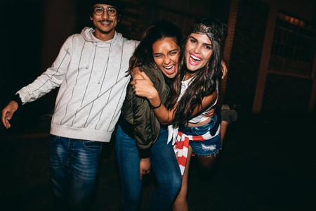 loco: Retrato de tres jóvenes amigos que se divierten juntos en fiesta al aire libre. Loco jóvenes mejores amigos pasando el rato.