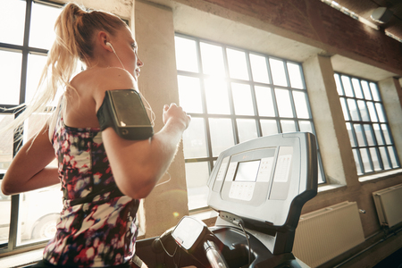 self conscious: Young focused female working out at gym jogging on a treadmill. Fitness woman doing running exercise in the health club.