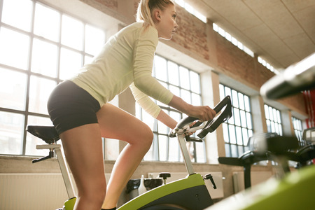 self conscious: Side view of focused young woman exercising on bike in health club. Fitness female workout on bicycle in gym.