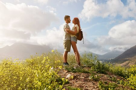 couple outdoor: Portrait of amorous couple in embrace standing on a hill top. Young man and woman in love standing together on a peak on a summer day. Stock Photo