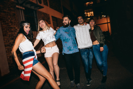 gente bailando: Alegre jóvenes caminando juntos en la noche y divertirse. Grupo multirracial de amigos que cuelgan hacia fuera en la noche.