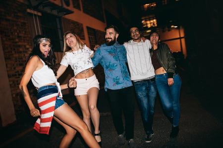 persone che ballano: Allegre giovani camminano insieme di notte e divertirsi. Gruppo multietnico di amici appendere fuori in serata.