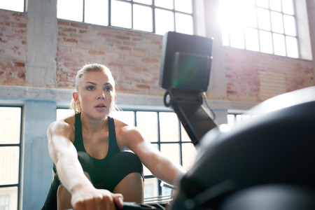 one young woman: Fit young woman working out on a rowing machine at the gym. Caucasian female doing cardio exercise in fitness club.
