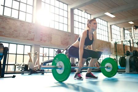 pesas: Entrenamiento fitness mujer decidida y fuerte con los pesos pesados ??en el gimnasio. Caucásica atleta femenina haciendo levantamiento de ejercicio en el gimnasio levantando. Foto de archivo