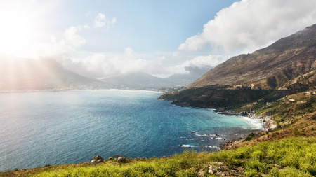 south africa: Wide angle view of beautiful landscape with bay of water and mountain range on a summer day. View of  Hout Bay from Chapmans peak Drive on atlantic coast of South Africa. Stock Photo