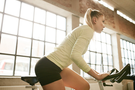 self conscious: Indoor shot of fit young woman working out on a stationary bike in gym. Determined caucasian female training on exercise equipment in health club.