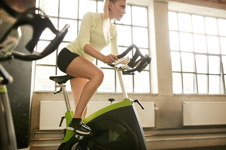 Fitness woman on bicycle doing spinning at gym. Fit young female working out on gym bike. Stock Photo