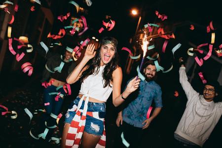 borracho: Retrato de los jóvenes locos que celebran al aire libre. Jóvenes amigos de fiesta al aire libre con bengalas y confeti en Nochevieja.