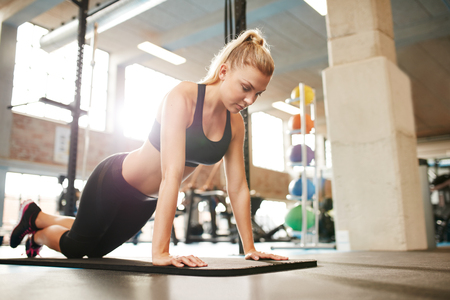 self conscious: Attractive young female doing push ups on exercise mat. Fitness woman working out in gym. Stock Photo