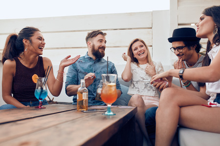 party table: Portrait of happy young people sitting together and laughing. Multiracial friends enjoying at a party with cocktails on table.