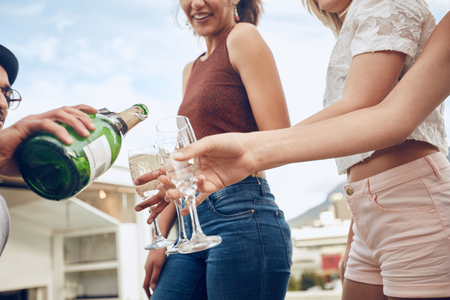 Man serving champagne to friends during party. Cropped shot with focus on hands and champagne glasses. Young people having champagne at party outdoors.