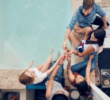 Bovenaanzicht van de groep van vrienden roosteren op feestje met een zwembad. Hoge hoek schot van jonge mensen zitten bij het zwembad met wijn. Mannen en vrouwen feesten bij het zwembad.