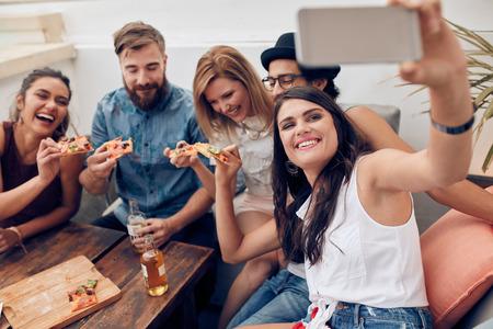 eten: Groep vrienden nemen selfie op een slimme telefoon. Jongeren eten pizza op feestje op het dak nemen selfie. Stockfoto