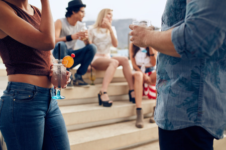 Cropped shot of a couple holding cocktails glasses while three people talking to each other in the background. Young people having rooftop party. Imagens