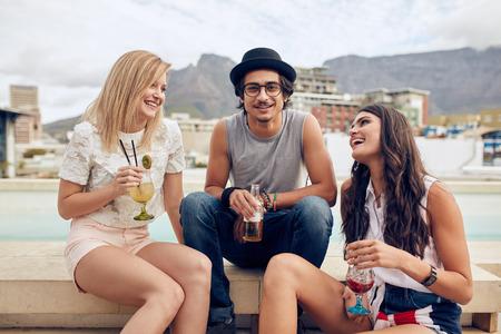 cocteles: Retrato de hombre joven fresco sentado con sus amigas disfrutando de bebidas. Los j�venes que cuelgan hacia fuera en una fiesta en la azotea. Foto de archivo