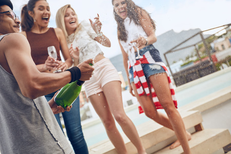 Party image of young man opening a bottle of champagne. Women standing by a swimming pool holding glasses and laughing. Young people enjoying party with drinks.