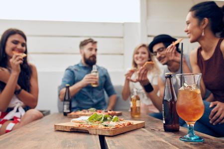 Gruppo di amici multietnici che godono della pizza e birra in partito. I giovani che hanno un partito. Focus su pizza e cocktail giace sul tavolo di legno.