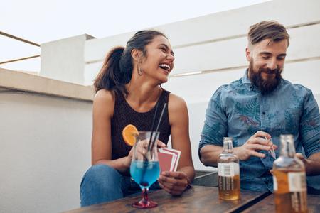 Pares que se sientan por una fiesta mesa y juegos de cartas. Feliz el hombre joven y una mujer jugando a las cartas durante una fiesta.