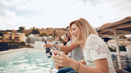best party: Young people drinking by the pool during party. Young friends laughing while sitting by a swimming pool. Men and women partying and having fun outdoors. Stock Photo