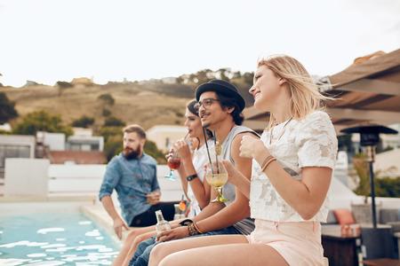 Glückliche junge Freunde am Pool mit Cocktail sitzen. Junge Leute am Pool mit den Füßen im Wasser während einer Party zu entspannen. Männer und Frauen genießen Dachparty. Standard-Bild - 50431720